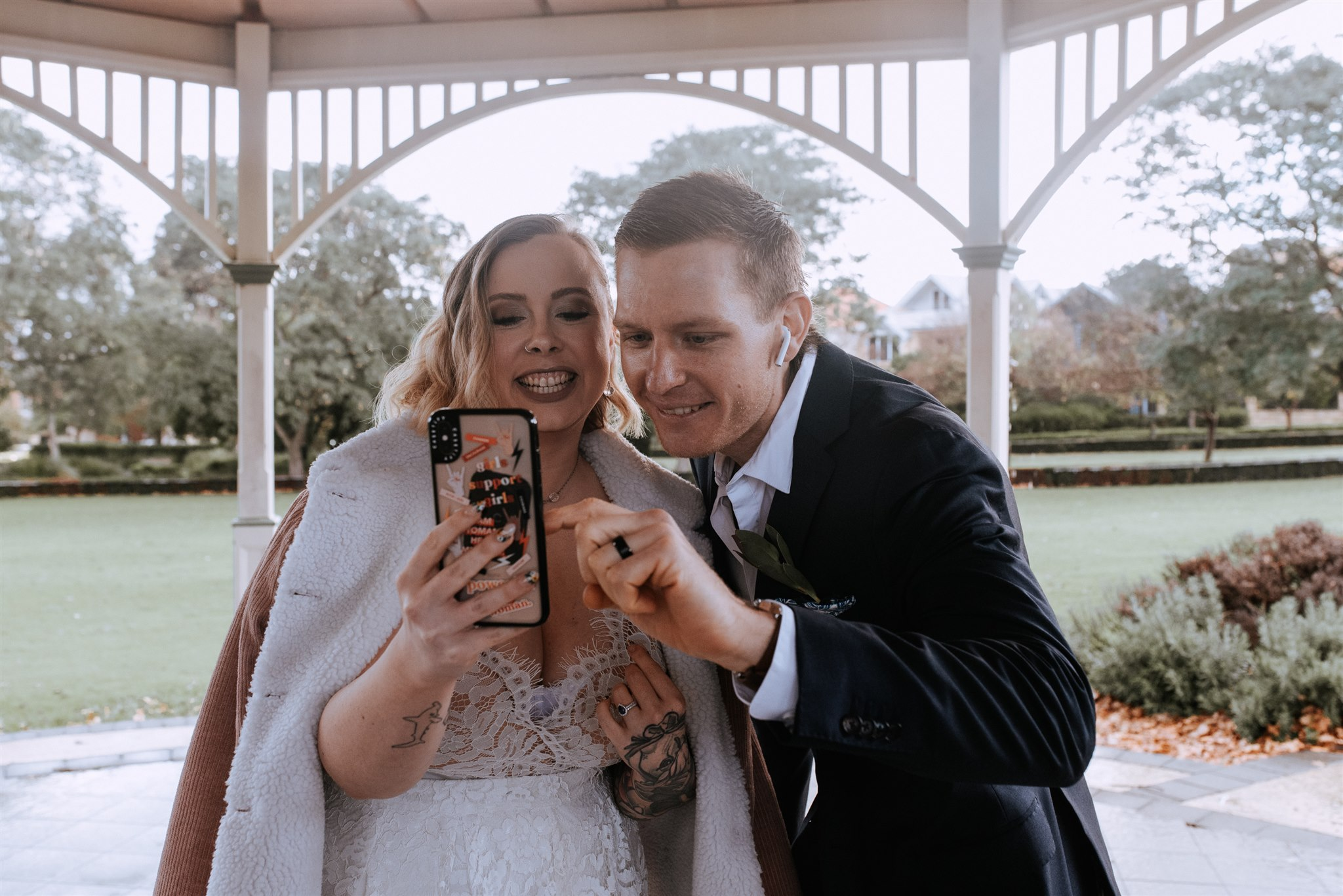 Woman in white wedding dress with veil smiling and holding a mobile phone with man in a navy jacket, smiling and pointing at the mobile phone