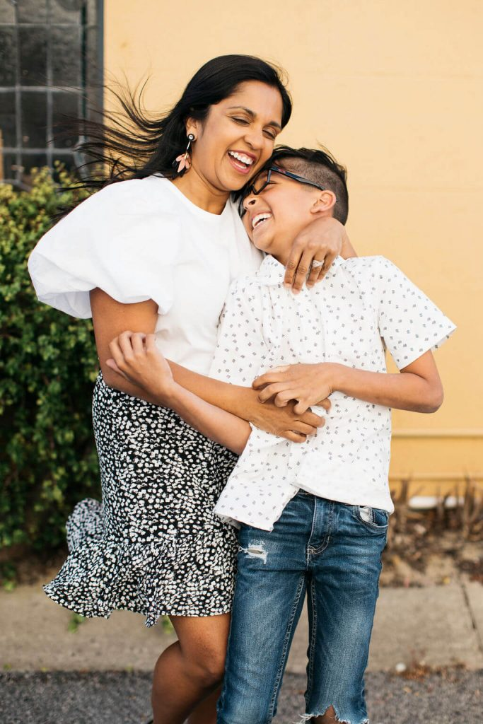 Mom and son holding each other and laughing